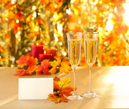 Champagne glasses for reception in front of autumn background and candles and placecard