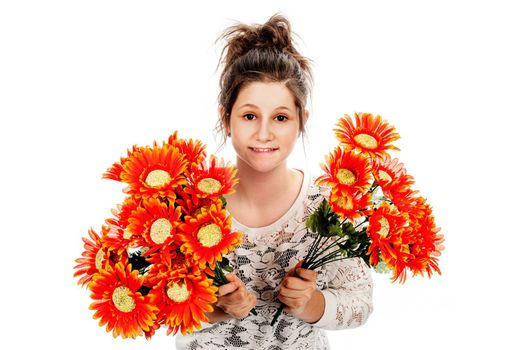 Guilty looking teenage girl seeking forgiveness with two bunches of fake flowers. Studio shot on white background.