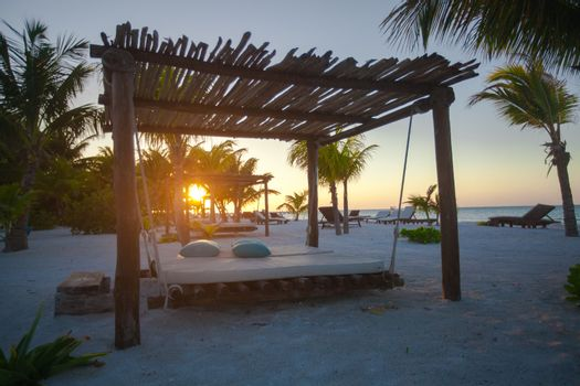 Beach beds among palm trees at perfect tropical coast at sunset