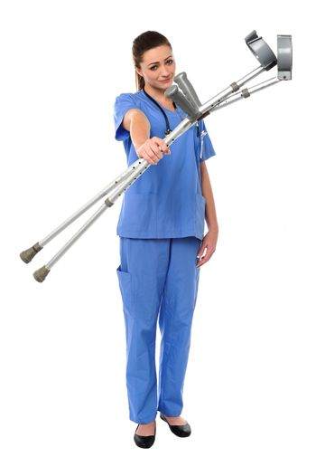 Sullen faced doctor displaying crutches