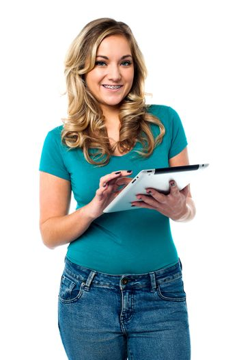 Cute girl surfing on a tablet, browsing internet