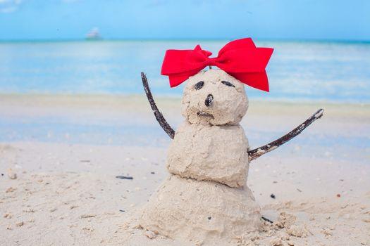 Little sandy snowman with bow on a sandy Caribbean beach