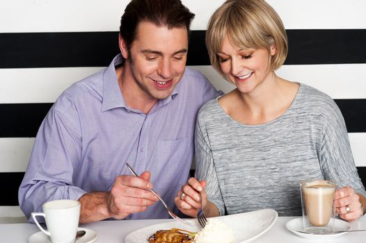 Beautiful middle aged couple enjoying coffee and trying new cuisine