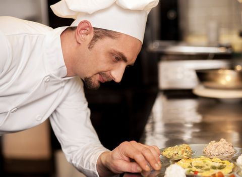 Satisfied chef analyzing dish before serving