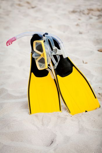 yellow fins and snorkelling mask on beach in summer