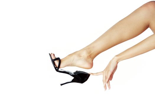 Woman hand and leg in black shoe against white background