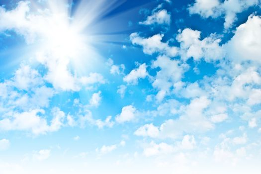 blue sky with sparce cumulus clouds and sun