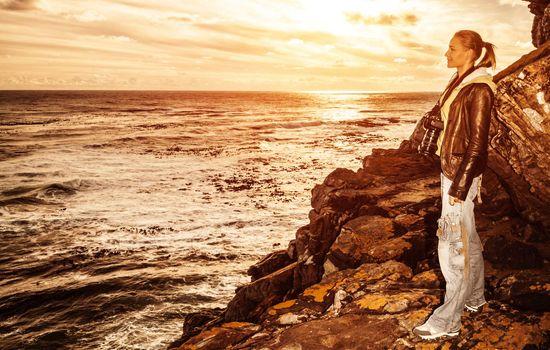 Tourist girl on sunset on the cliff