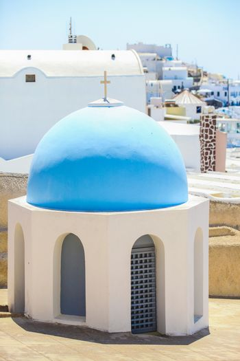 Small church with a blue dome and the view of the caldera