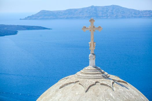 traditional white church with a cross on the dome on Santorini
