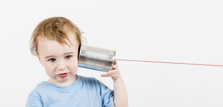 young, disappointed child listening to tin can phone. caucasian child in horizontal image