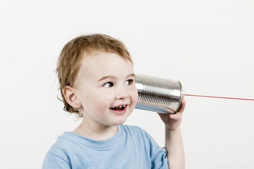 happy child in light grey background listening to tin can phone. horizontal image
