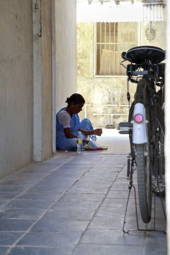 Vertical capture of an Indian maid sat on the floor in the shade inside an alleyway having lunch which has been wrapped in newsprint. Typical shot in Indian with bicycle parked close by