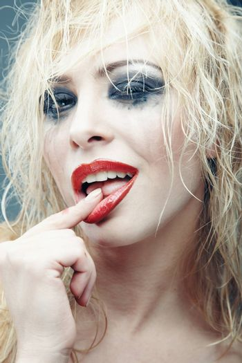 Young blond lady with bizarre makeup. Vertical studio photo. Artistic colors added