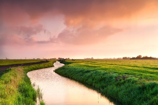 dramatic sunrise over canal in farmland