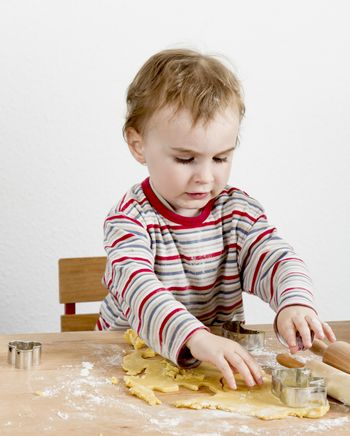 child at wooden desk making cookies. vertical image