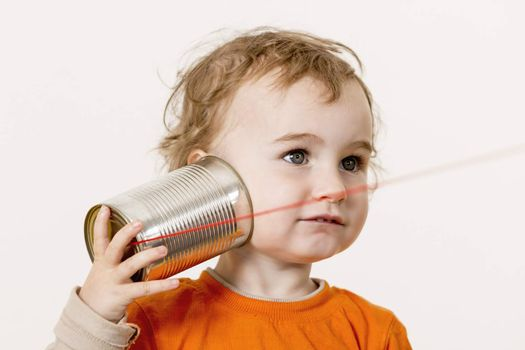 young child listening big to tin can phone. horizontal image with neutral light grey background