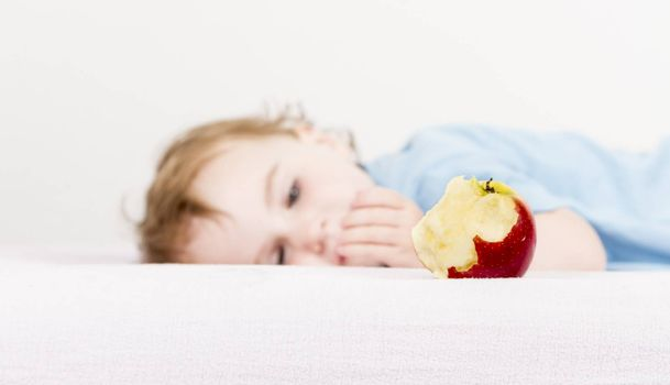 red apple with blurred, sleeping child in background