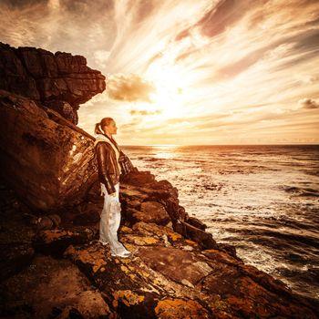 Photographer woman on rocky seashore
