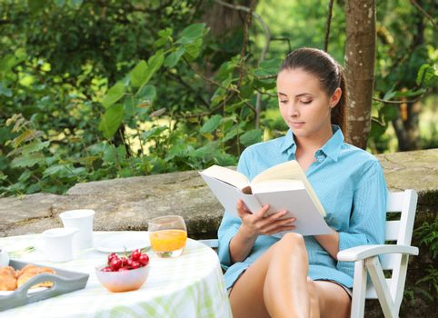 Beautiful girl reading a book outdoors enjoying a summer day