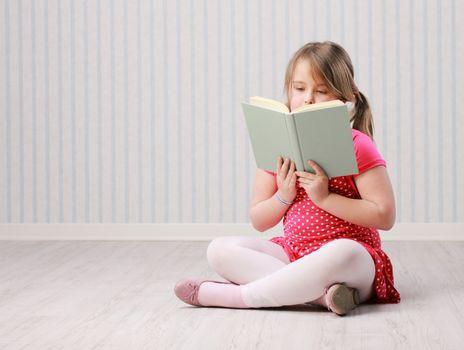 Beautiful little girl reading a book on floor
