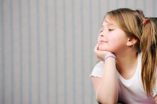 Portrait of a little beautiful girl looking at copy space