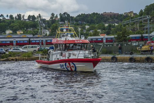 Rescue boat RS 142, Horn Flyer escorts MS Sj��kurs with NRK through Ringdalsfjord, heading for the port of Halden. Photo is shot from Halden harbor, Halden, Norway.