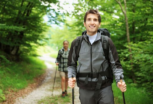 Young couple enjoying a nordic walk, man is smiling