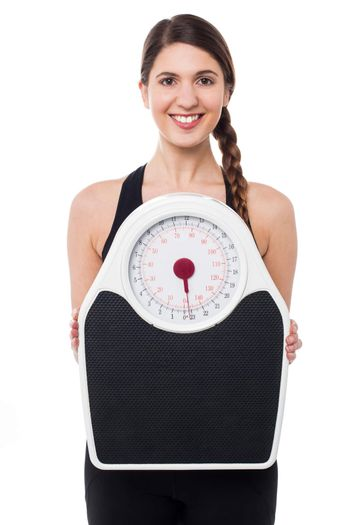 Young girl holding weighing machine