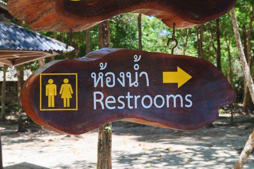 Restroom sign on wood board