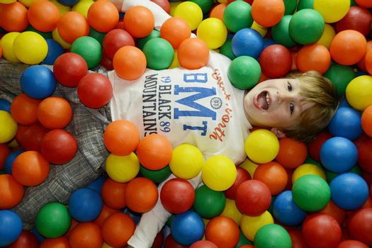 little happy kid playing with colored balls
