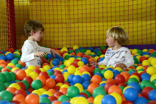 little happy kids playing with colored balls
