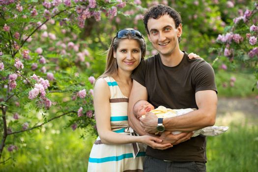 Young caucasian couple with newborn son outdoors in spring