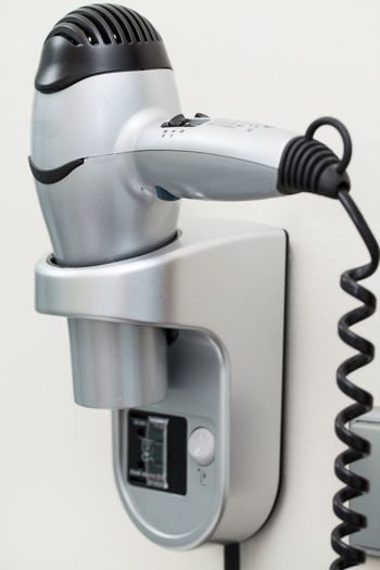 Hairdryer with cord attached to a wall