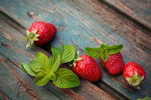 Fruit food concept. Fresh strawberries and mint leaf on wood