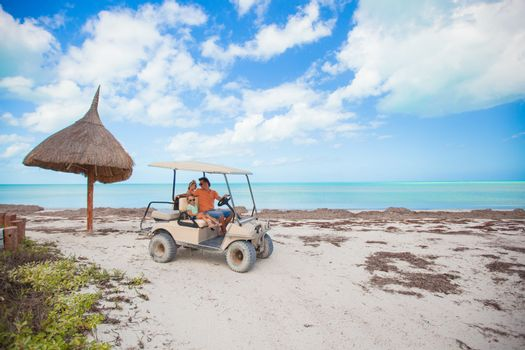 General view golf car with family inside on an exotic beach