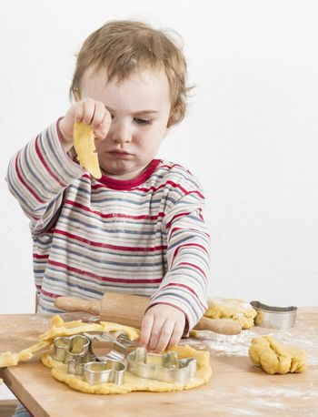 young child working with dough on wooden desk with flour. Vertical image