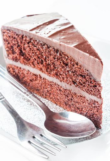 Close up piece of chocolate cake with spoon and fork