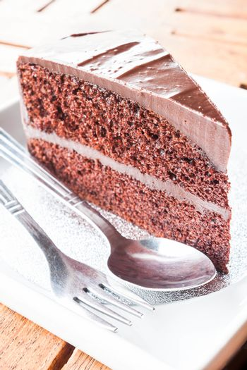 Piece of chocolate cake serving with spoon and fork