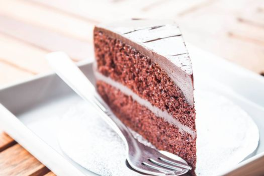 Chocolate cake serving on white dish with spoon and fork