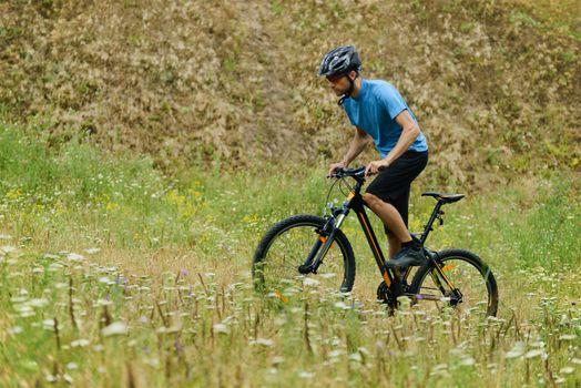 Mountain Biker Riding His Bike Through the Meadow