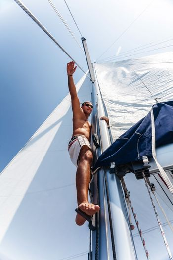 Cute sailor fix sail, active lifestyle, summer holidays, water journey, yachting sport, man on vessel, marine lifestyle