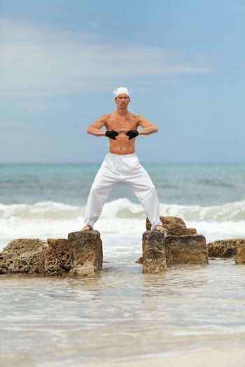 healthy man doing pilates yoga meditation on beach summer freedom