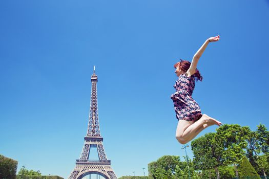 Young attractive happy woman jumping for joy against Eiffel Tower in Paris, France