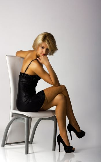 young beautiful woman in black dress sitting on a chair in studio