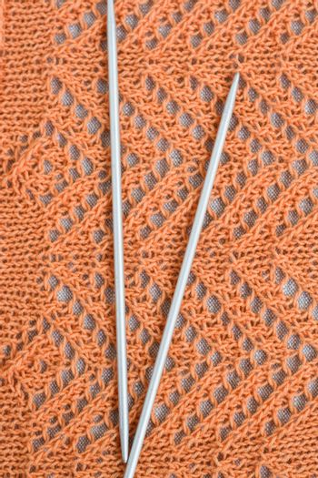 Openwork pattern with orange thread and a pair needles