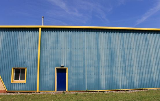 Exterior of industrial warehouse building in blue and yellow.