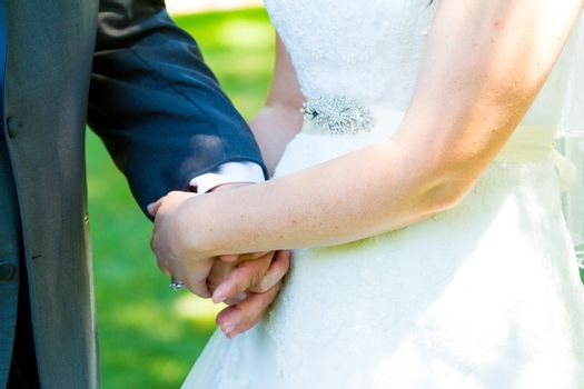 This bride and groom hold hands romantically while kissing on their wedding day.