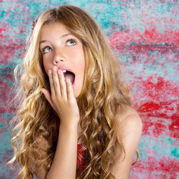 Blond kid girl surprised expression hands in face