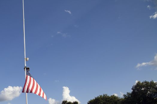 American flag at half mast with top of house and tree tops in the background